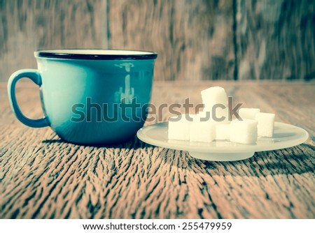 sugar cube and blue coffee cup ; vintage filtered style - stock photo