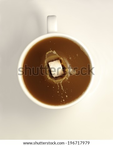 sugar cube splashing into a white cup of coffee on a white saucer. - stock photo