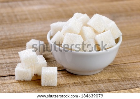 Sugar cubes in bowl on wooden table - stock photo