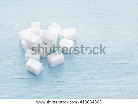 Sugar cubes on blue background. White Sugar. Selective focus