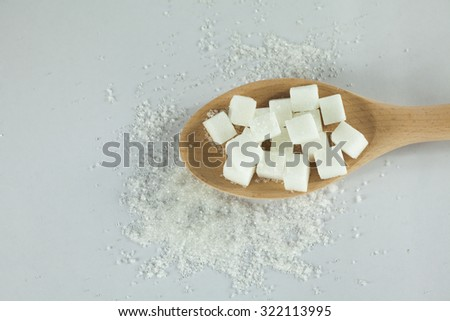 Sugar Cubes on Spoon with granulated sugar on Isolated White Background - stock photo