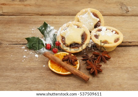 Sugar dusted mince pies with star anise, cinnamon, dried orange and holly on old weathered wood