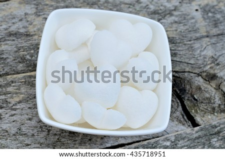 Sugar heart in white bowl on rustic table - stock photo