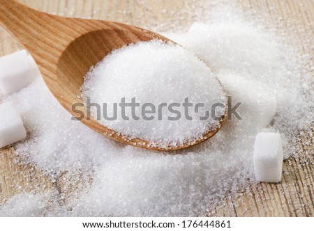 Sugar in a wooden spoon . Selective focus - stock photo
