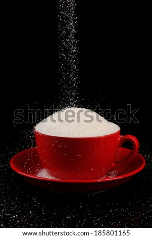 Sugar in cup isolated on black - stock photo