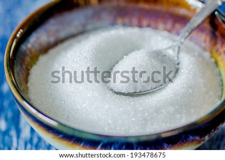 sugar in silver spoon on wooden background - stock photo