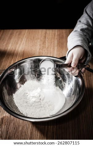 Sugar is being added to some flour in a mixing bowl. - stock photo
