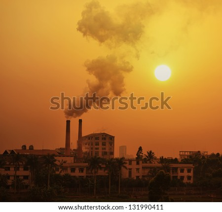 sugar mill polluting the atmosphere with smoke and smog - stock photo