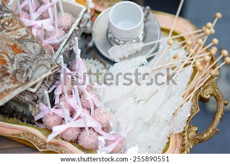 Sugar on sticks and pink pop cakes on tea tray - stock photo