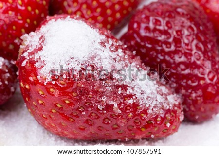 Sugar on the fresh strawberries on the plate.