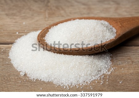 Sugar on wooden table. Selective focus.