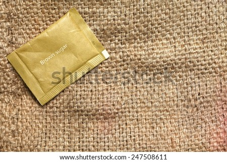 Sugar pack put on the coffee bean sack or gunny sack  brown color represent texture surface background. - stock photo