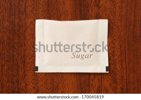 Sugar packet on the wooden table           - stock photo