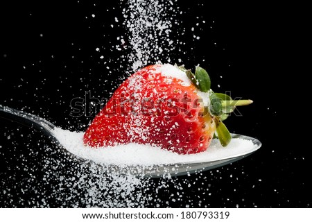 Sugar pouring over a strawberry on a spoon with a black background