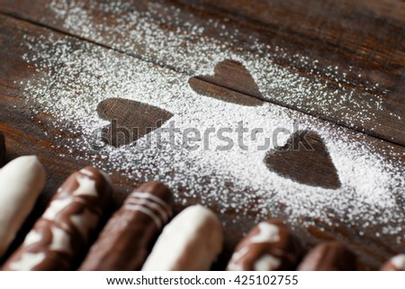 Sugar powder hearts and candies close-up. Dark background decorated in the form of hearts. Focus on decorated wooden background. Front view - stock photo