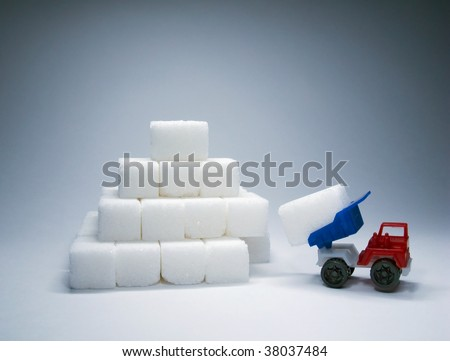Sugar pyramid under construction and toy truck - stock photo