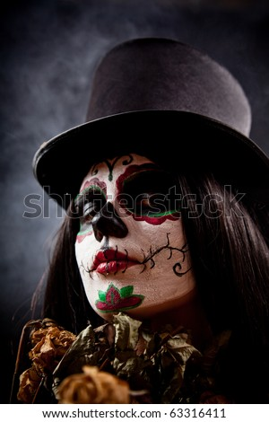 Sugar skull girl in tophat holding dead roses, studio shot - stock photo