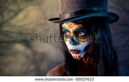 Sugar skull girl in tophat, in the forest - stock photo
