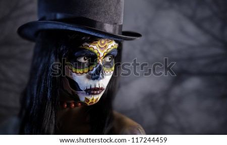 Sugar skull girl in tophat in the forest, Halloween theme - stock photo
