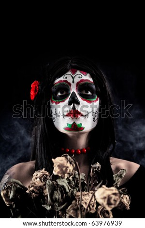 Sugar skull girl with dead roses, studio shot over black smoky background