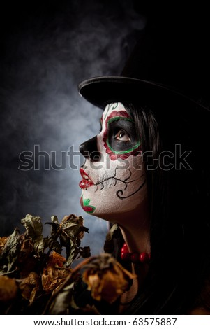 Sugar skull woman in tophat, holding dead roses, studio shot - stock photo