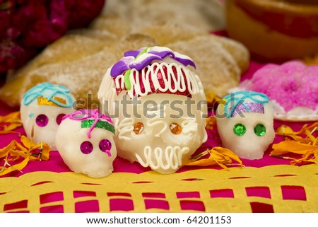 Sugar skulls from a day of the day Mexican holiday Dia de los Muertos with an offering background and cut out paper in front. - stock photo