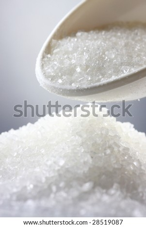 Sugar & spoon, close-up shot, shallow DOF. - stock photo