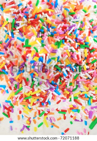 Sugar sprinkles on top of a icing birthday cake. - stock photo