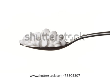 Sugar substitute pills in a spoon isolated on white - stock photo