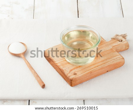 Sugar syrup in a glass bowl on a white wooden background - stock photo