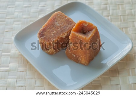 Sugarcane concentrate - an Indian jaggery cakes on white plate - stock photo