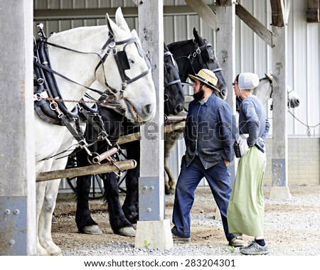 SUGARCREEK, OHIO -  May 20, 2015:  Amish couple watching over their horses by a white barn.  Shallow depth of field with focus on the woman. - stock photo