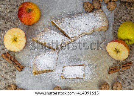 Sugared Homemade Apple Strudel on a Baking Paper, Walnut, Cinnamon and Apple Top View  - stock photo