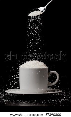 Sugarfall. A cup of coffee with a hill of sugar and a spoon. Concept of addiction to sugar.  Black and white photo. - stock photo