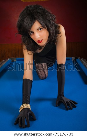 Suggestive and beautiful young brunette with black gloves crawling on a pool table