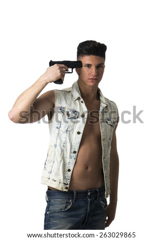 Suicidal attractive young man in an unbuttoned shirt standing with a serious expression pointing a gun at his head isolated on white - stock photo