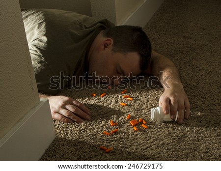 suicidal man passed out dead after consuming a lot of pills  - stock photo