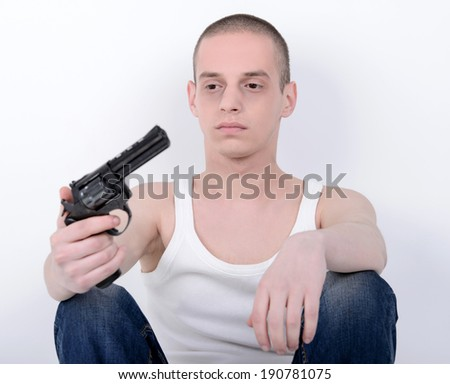 Suicide. Depressed young man holding gun near his head - stock photo