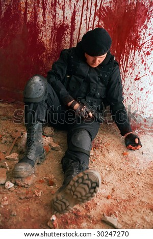Suicide near the blood wall. Focus point on the body. - stock photo