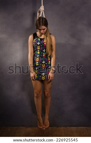 Suicide simulation. Young caucasian hanged woman - stock photo
