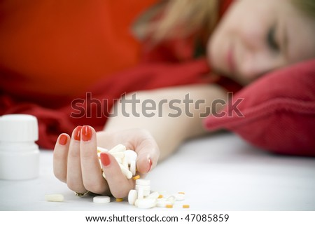 suicide test -  young depressive woman lying on red pillow, focus for drugs - stock photo