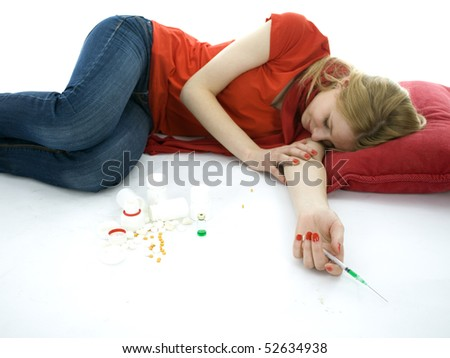 suicide test -  young depressive woman lying on red pillow, focus on drugs - stock photo