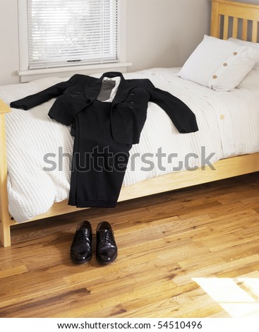 Suit and shoes on bed - stock photo