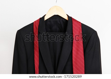 Suit and tie on hanger on gray background - stock photo