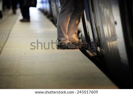 Suit entering eveing train - stock photo