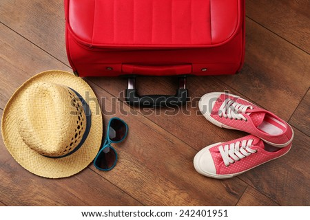 Suitcase and tourist stuff on floor close-up - stock photo