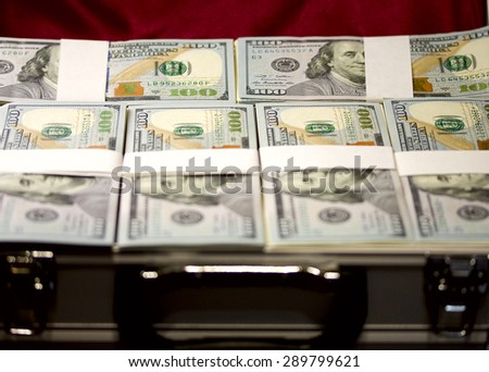 Suitcase filled with the lid open pack of dollars - stock photo