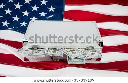Suitcase of money with hundred dollar on flag - stock photo