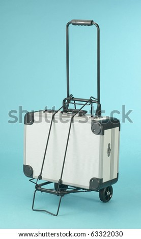 suitcase on a cart on blue background - stock photo