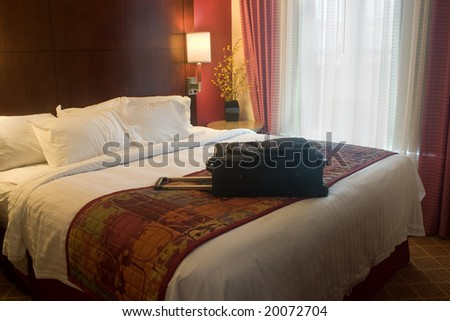 suitcase on bed in luxury hotel - stock photo